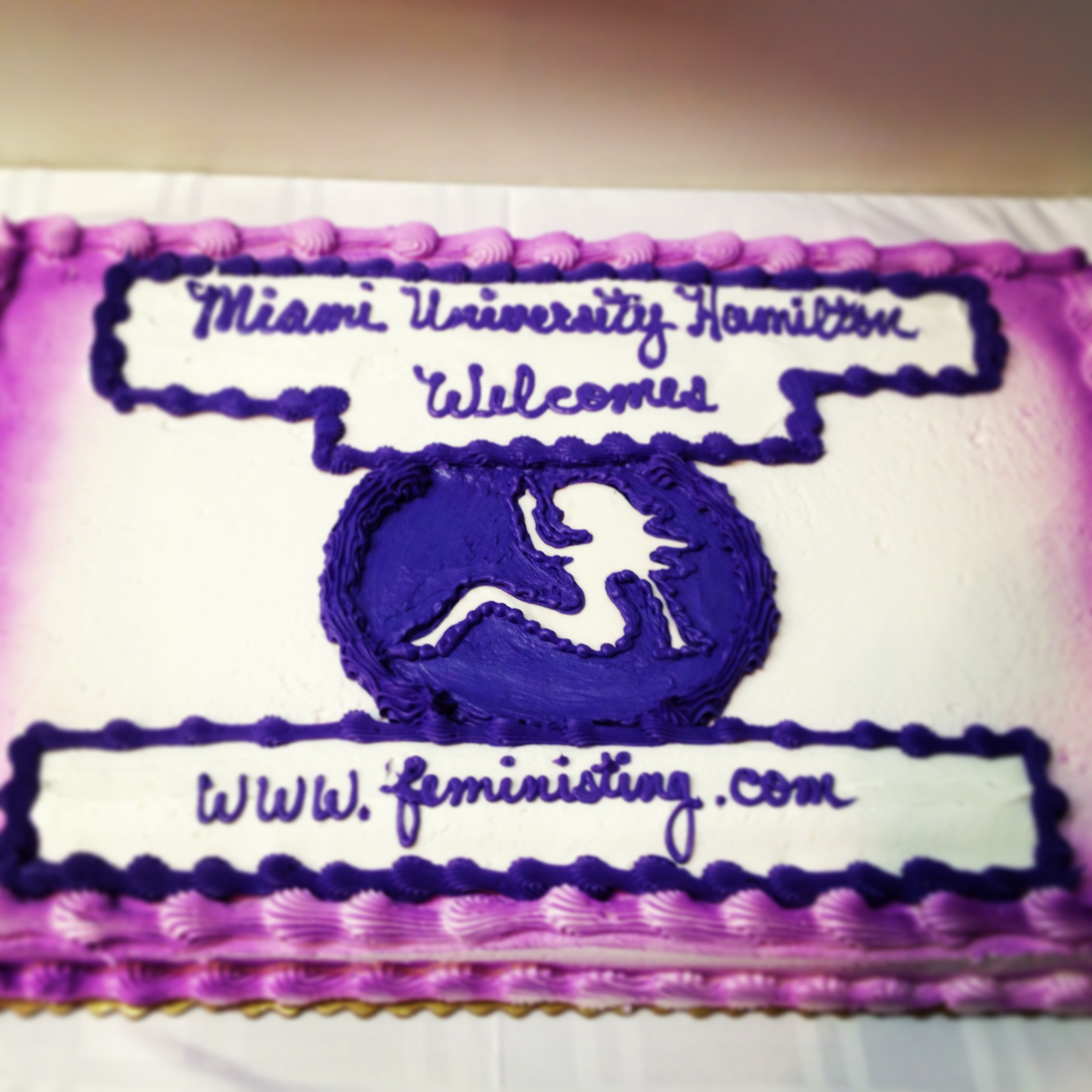 Purple cake with the Feministing mudflap girl and website url