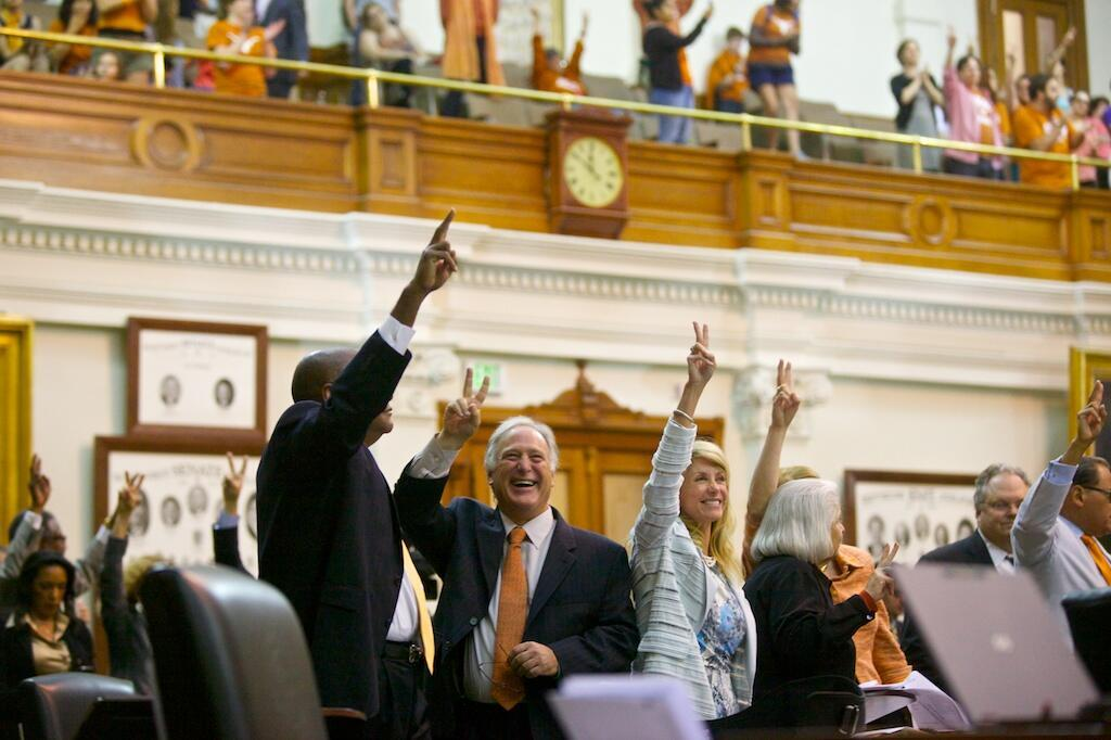 Wendy Davis and others hold up two fingers for a no vote