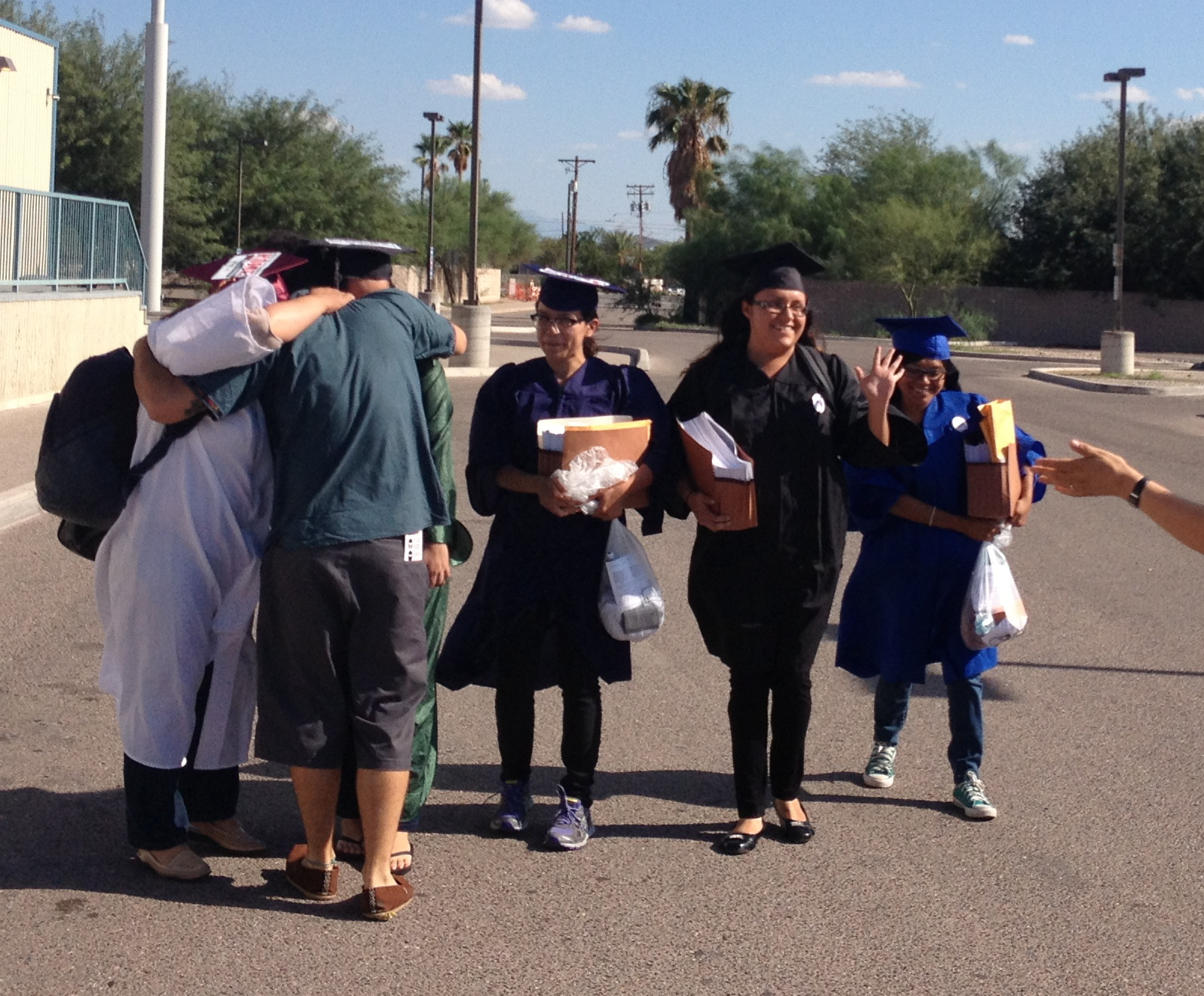 Women of the Dream 9 in graduation attire walking and hugging