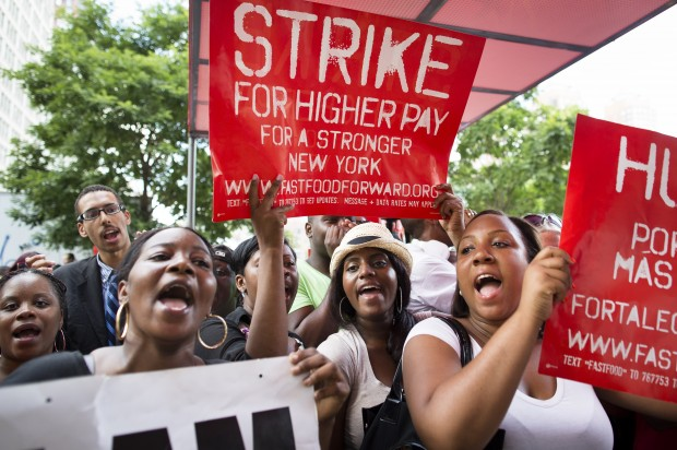 "Women protesting and holding up signs ""Strike for higher pay"""