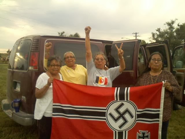 Lakota women stand with a captured neo-Nazi flag