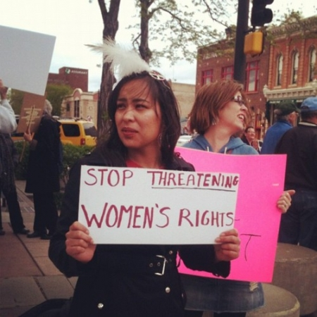 "Native woman protestor holding sign saying ""stop threatening women's rights"""