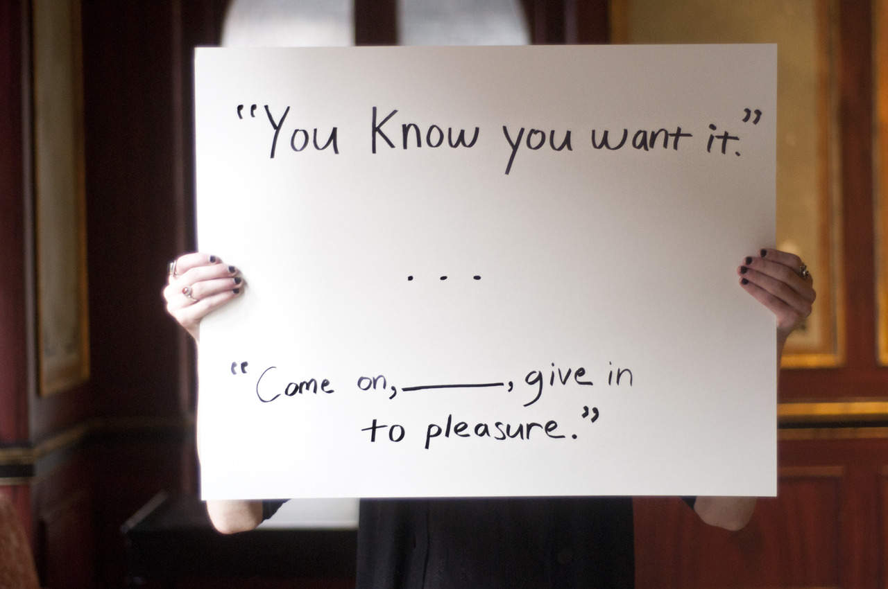"person holding sign saying, ""You know you want it. Come on __ give in to pleasure."""