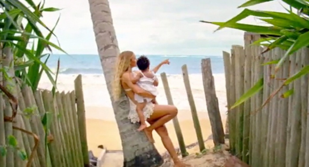 Beyoncé holding baby Blue Ivy and looking out at the ocean.