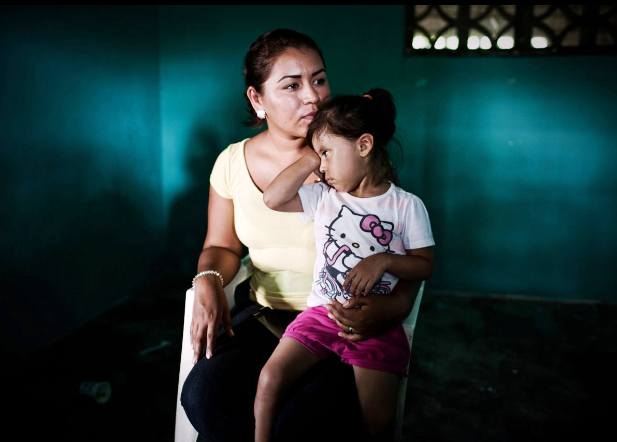 Mexican woman sits with her daughter in her lap.