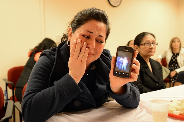Woman shows her two sons on her phone, crying as she tells how she misses them.