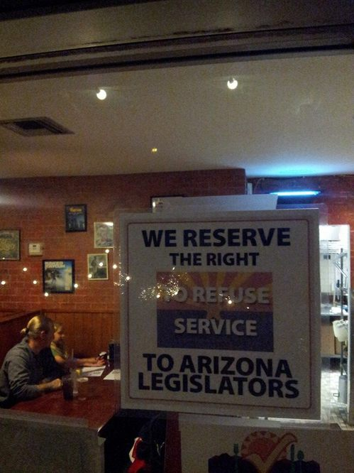 Sign in the window reads: We reserve the right to refuse service to Arizona legislators
