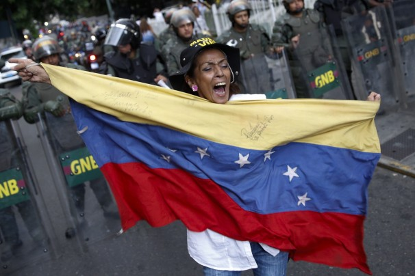 Venezuelan woman holding flag in front of riot police