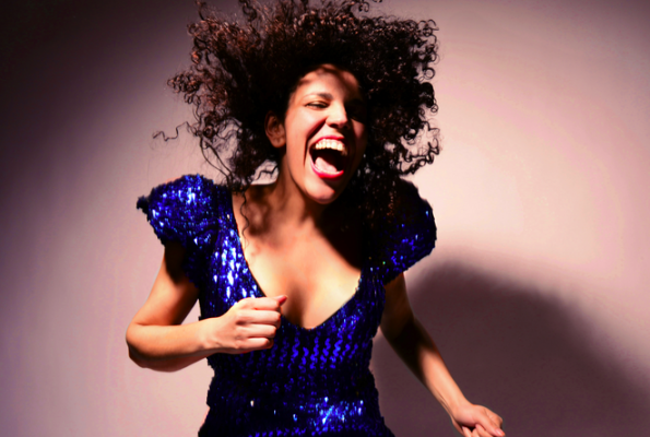 xenia rubinos laughing in a blue sparkly dress