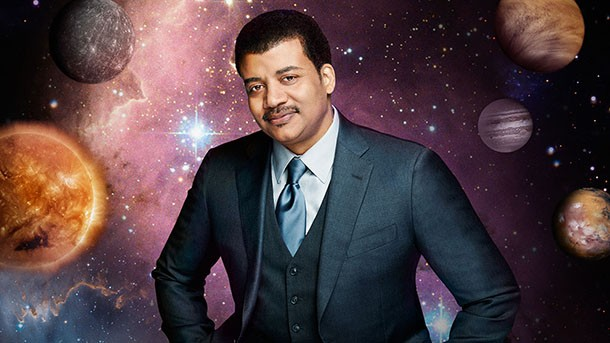 Neil deGrasse Tyson in a three-piece suit and tie, in front of a cosmic landscape