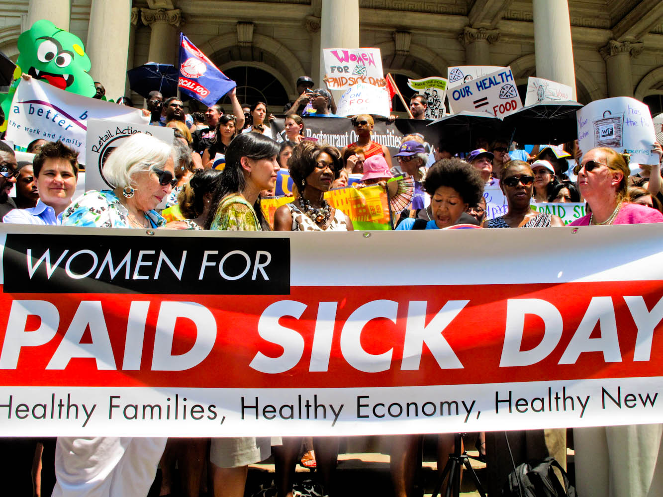 Women for Paid Sick Days sign and protestors