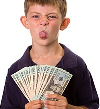 boy sticking out tongue and holding dollar bills