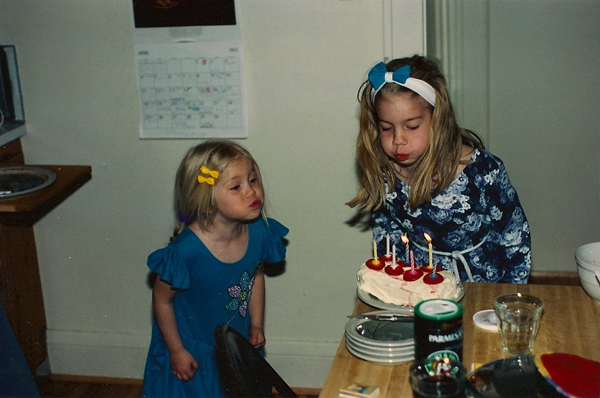 Maya and her sister blowing out the candles on a birthday cake when they were children.