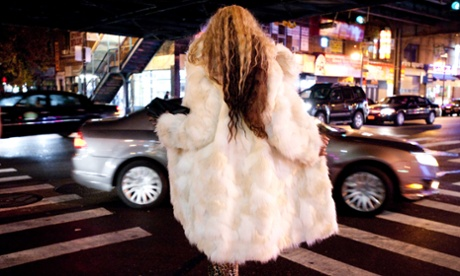 Woman shot from behind, with long hair and a long white fur coat that she is opening up in the direction of a car driving by.