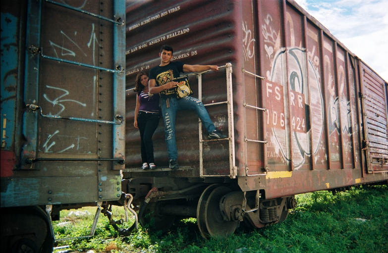 woman and man posing for a photograph on freight train