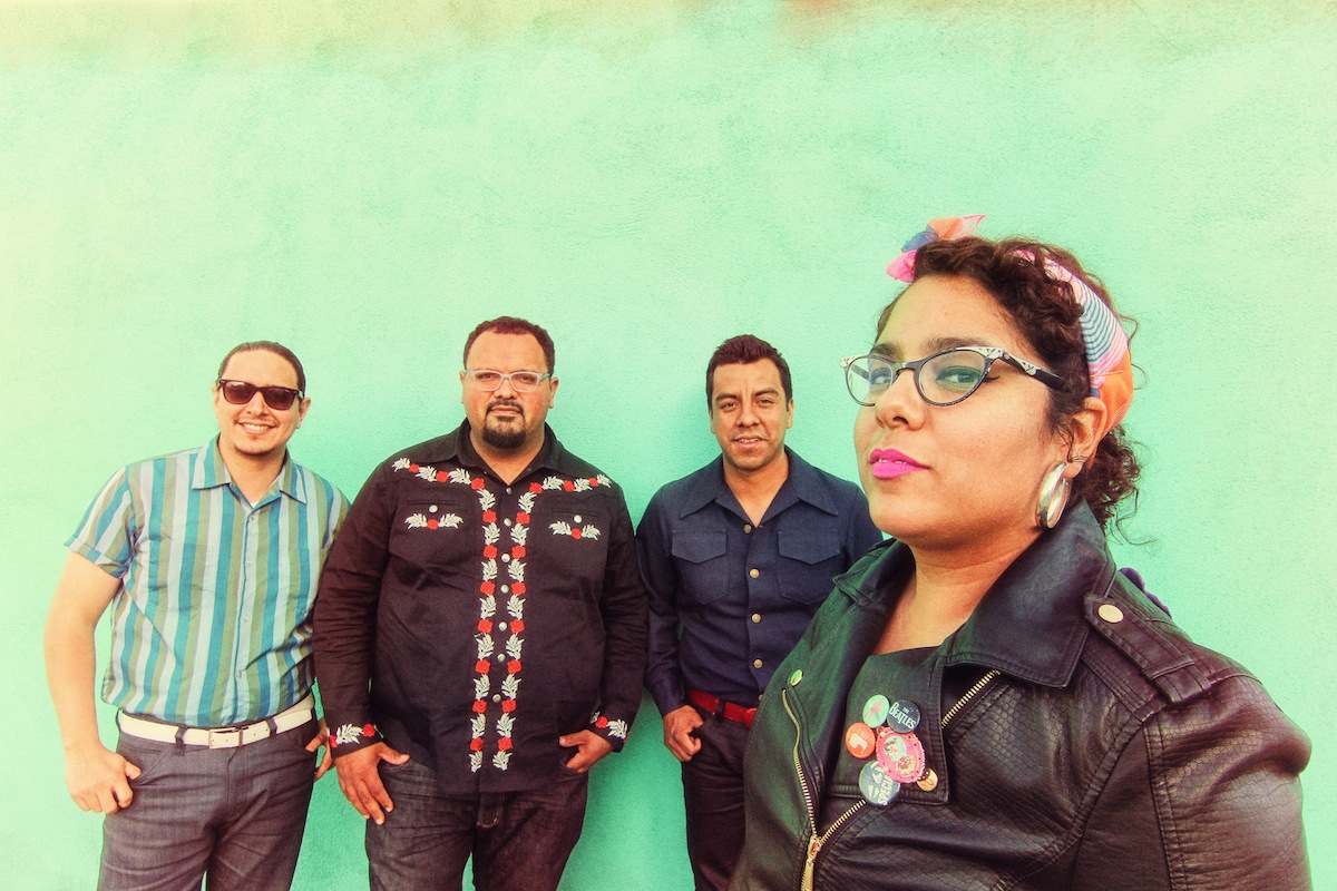 Band members against a green wall. La Marisoul wears cat-eye glasses, a bold pink lip, and a leather jacket. The guys are wearing button-ups. Miguel's is embroiderered in white and red.