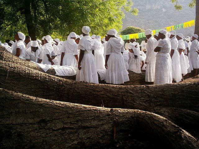 Standing among huge tree roots, a group of black women dressed all in white gather, their backs to the camera.