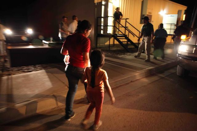 Photo taken at night of a young woman holding a baby on her hip, while holding her daughter's hand with the other. They are walking towards a detention facility.