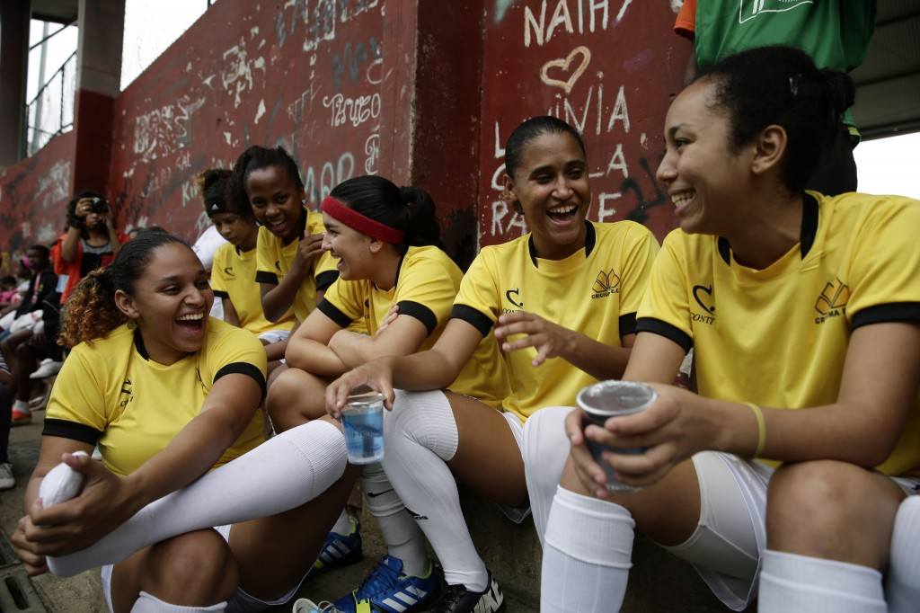 A group of young Brazilian girls wearing soccer outfits laugh together.