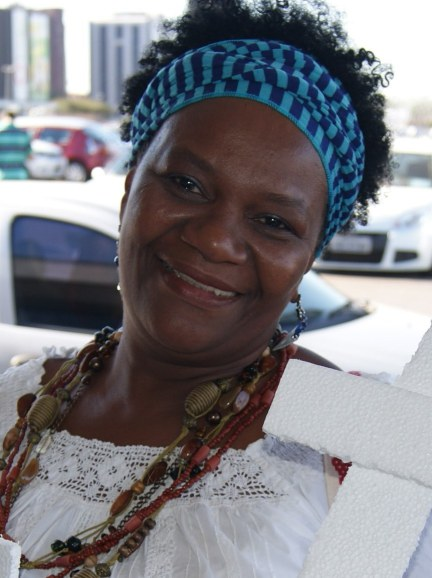 An Afro-Brazilian woman wearing a scarf around her hair, a beaded necklace and a white lacy shirt smiles at the camera.