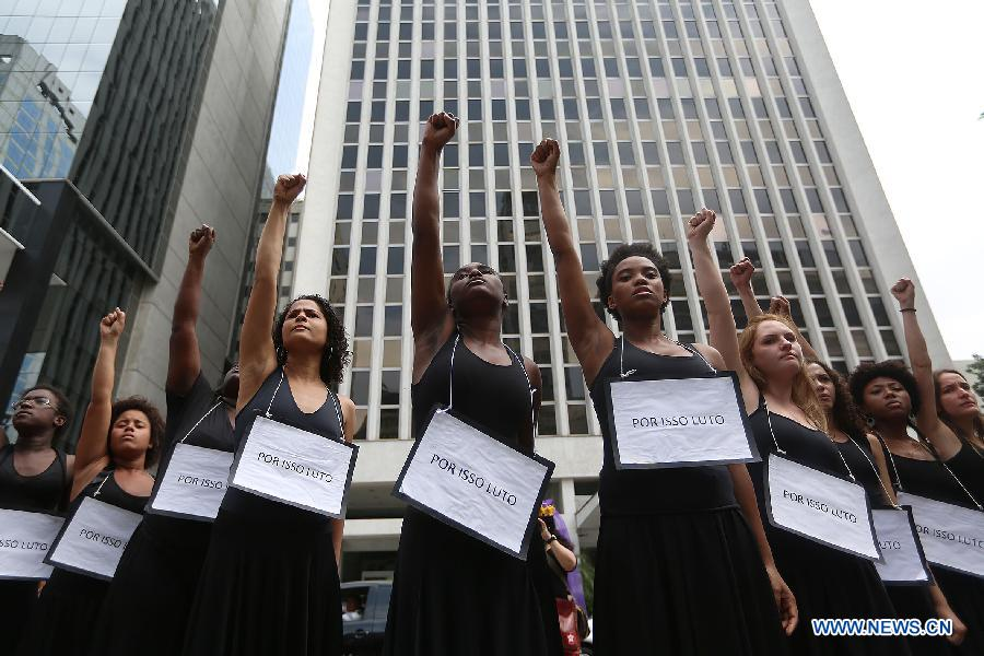 "A group of women wearing all black raise their fists in the air, serious expressions on their face. They all wear signs that read ""for this I fight."""