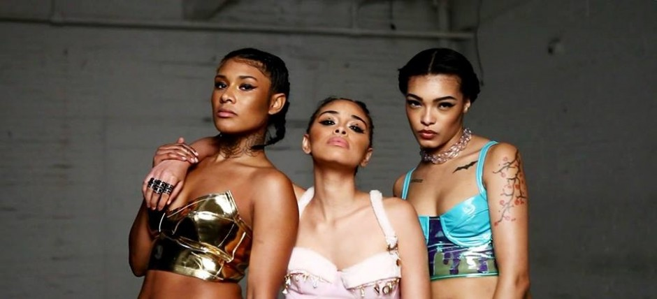 Three women of color, looking straight into the camera, chins up, wearing bustiers by AKV