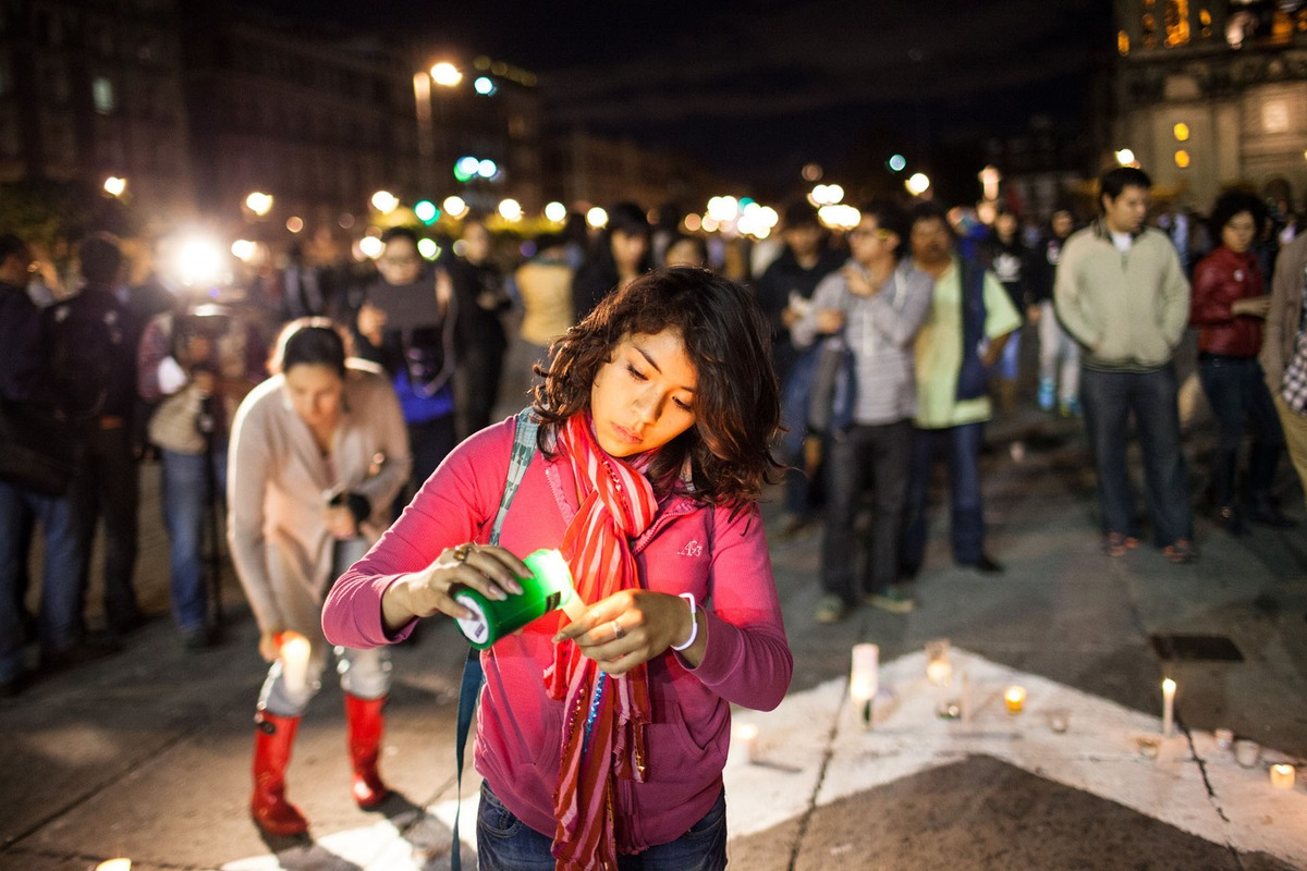 A young woman stands in front of a crowd of protestors, lighting a candle. It's dark outside, and her face is lit up.